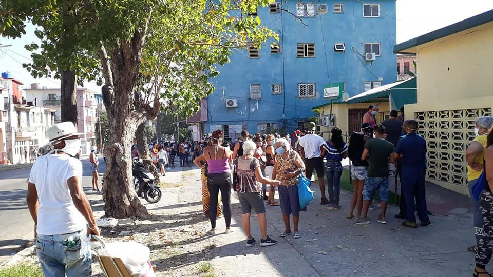 Queues of Cubans lining up to buy food and wearing face masks in a street of Las Tunas during COVID-19 outbreak